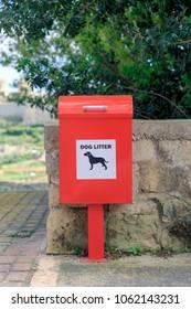 A red doggie litter bin