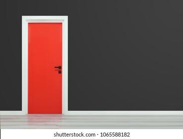 Red door with black handle in a dark grey wall