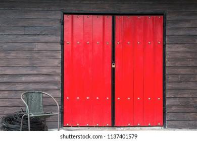 Red door  and Brown wooden wall with wicker chair in front of the door.