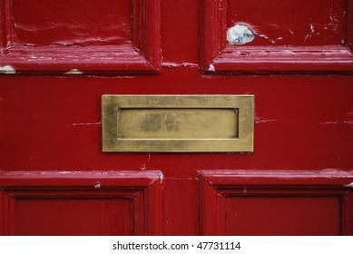 Red door with golden letterbox