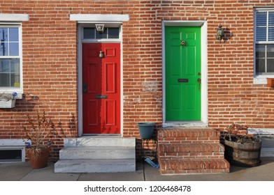 A red door and a green door, contrasting colors, side-by-side on a red brick townhouse.