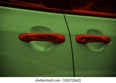 Red door knobs of a green car unique photo