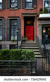 a red door on a colorful brownstone building in an iconic neighborhood of Brooklyn, New York City