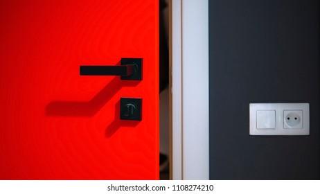 Red door small opening to a dark room, peeking in. Light switch