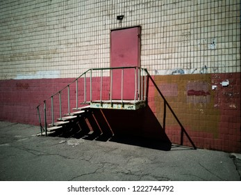 Red door with stairs on brick old wall. Zaporozhye, Ukraine, 24 August 2018.