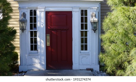 A red door with white trim adorned by lanterns on either side, and green shrubs.