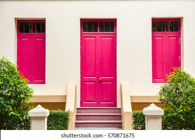 Red Door, red window on Cream Wall on red staircase with small tree background