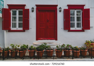 Red door and windows at the streets of Mykonos, Greece.