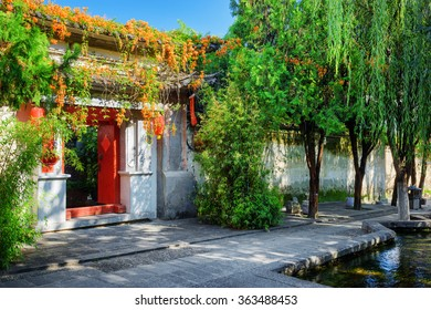 Red doors leading into courtyard of traditional Chinese house in Dali Old Town, Yunnan province, China. Beautiful view of street with flowers and green trees at the ancient city.
