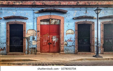 Red Doorway and covered windows on a crumbling building in Oaxaca, Mexico