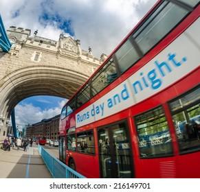 Red Double Decker Bus speeding up under Tower Bridge.