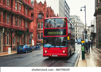 Red double-decker bus at the street of Birmingham, UK. Old building of the historical part of the city. Cars, famous restaurants and pubs