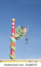 Red dragon climbing the pole. Northern Chinese temple, blue sky.