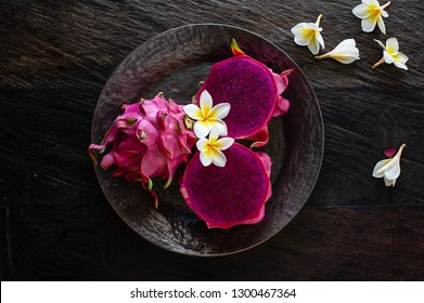 Red Dragon Fruit, tropical fruits in Indonesia & Southeast Asia. Cut into half in a black round texture ceramic plate on top of dark teak wood background w Frangipani flowers scattered