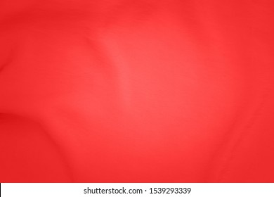 Red draped fabric texture, close up. Red cloth texture, close up. Red fabric drape background. Red pink background from draped cloth. Coral color Soft silk cloth or satin texture