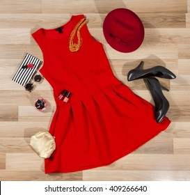 Red dress and accessories arranged on the floor. Woman pleated dress with accessories, purse, hat, high heel shoes and vintage sunglasses.