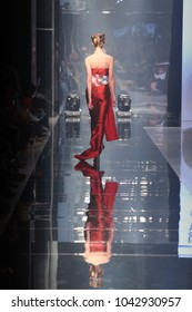 Red dress Model walk back on mirror Runway Fashion Show catwalk with reflection on floor lighting along walk way, background stage ramp