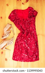 Red dress on wooden background. Flat lay, top view. Woman colorful fashion clothes and accessory concept.