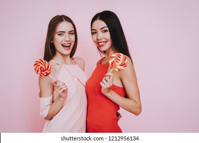 Red Dress. Pink Dress. Pink Background. Celebrating Women's Day. Two Girls. Smiling Girl. Happy Woman. Happy Emotions. International Party. Beautiful Woman. Big Lollypop. Womans with Lollypops.