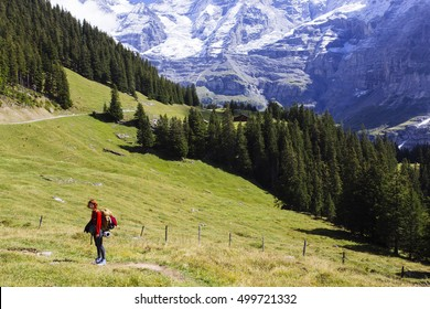 A red dressed girl standing on the path full of sun light in the mountains in Switzerland.