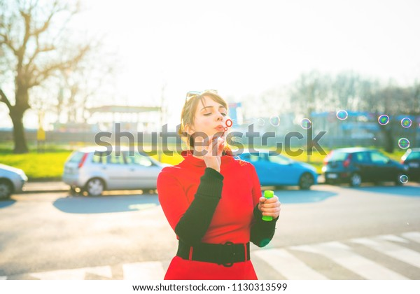 red dressed young woman outdoor playing bubble soap back light - happiness, having fun, innocence concept
