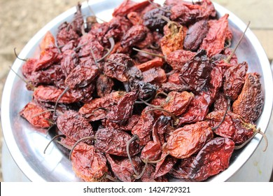 Red dried king chillies on a plate. The Naga King Chilli (Capsicum chinense Jacq) is one of the hottest chillies in the world. This chilli is native to the north eastern region of India in Manipur and
