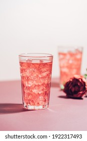 Red drink cocktail or lemonade with ice in a glass on pink background.