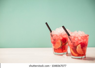 Red drink with ice. Cocktail making bar tools, raspberry, lime, oranges and mint leaves. Raspberry mojito on blue background