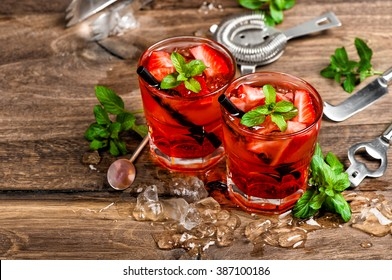 Red drink with ice, mint leaves and strawberry. Cocktail making bar tools