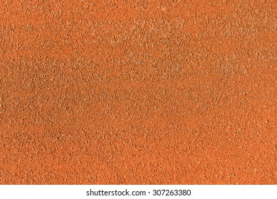 Red dry grungy clay tennis background texture. Tennis court macro
