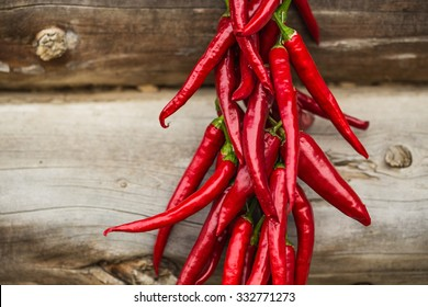 Red dry peppers hanging on wooden wall