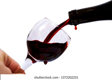 red dry wine of ruby ​​color is poured into the glass from the bottle with a stream, drops of wine, the hand is holding the glass, isolate on a white background