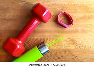 Red dumb bells with digital sport tracker and solid sports water bottle