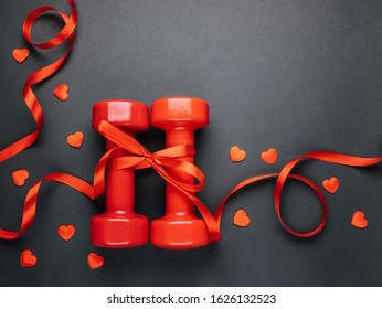 Red dumbbells wrapped in red ribbon as a gift for Valentine's Day.