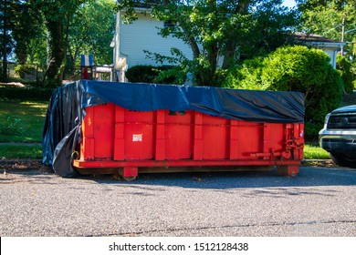 Red dumpster with black plastic liner on a asphalt street near the side of a house with trees in the background