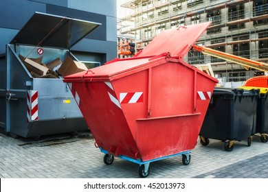 Red dumpster, recycle, waste and garbage bins near new office building. Construction site on background