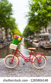 Red dutch miniature bicycle with cute details at Amsterdam canal scenery background, tulip flowers in wooden crate, leather saddle, bright tires (copy space)