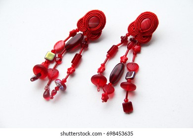 Red earrings on white background