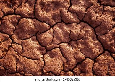 Red earth texture. Barren soil. Drought concept. Dry ground texture. Barren soil. Drought concept.