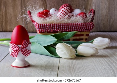 Red Easter egg in egg cup with bow on wooden table top. Easter eggs in basket, white tulips.