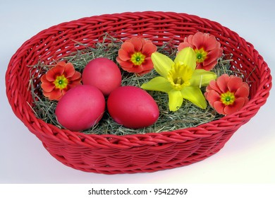 red Easter eggs and flowers in a basket