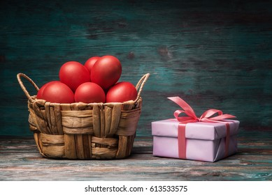 Red Easter eggs and gift box over wooden background