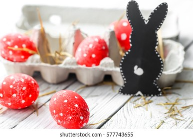 Red Easter eggs white polka dots in a cardboard tray with rabbits on wooden background, holiday concept