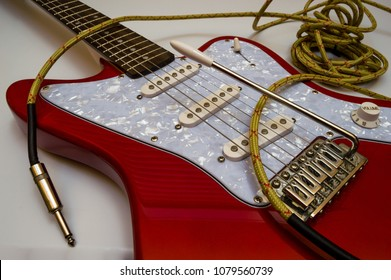Red Electric Guitar And Long Vintage Yellow Jack Cable To Connect In An Amplifier Musical