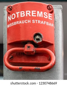 "Red emergency brake to stop a large rolling staircase, with German inscription ""emergency brake, misuse punishable"""