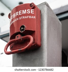 """Red emergency brake to stop a large rolling staircase, with German inscription """"emergency brake, misuse punishable"""""""