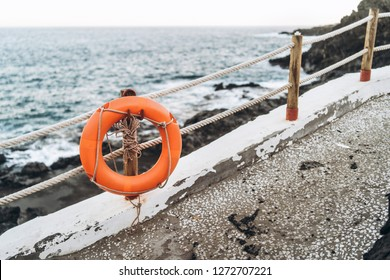 Red emergency lifebuoy hanging on fence near beach