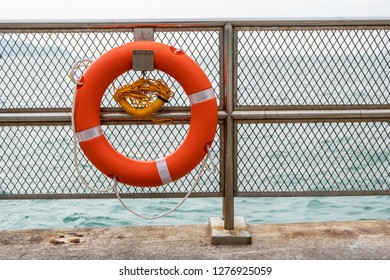 Red emergency lifebuoy hanging on fence near sea