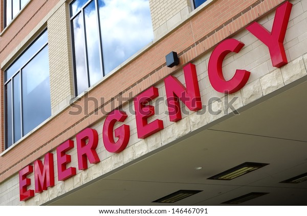 Red emergency room sign on the side of hospital with windows