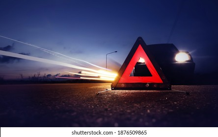 Red emergency stop sign (red triangle warning sign) with long-exposure of traffic light trails at nigh.